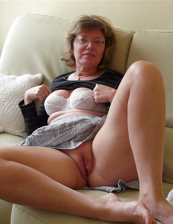 Grandmother exhibitionist in large sunglasses posing in the kitchen nude