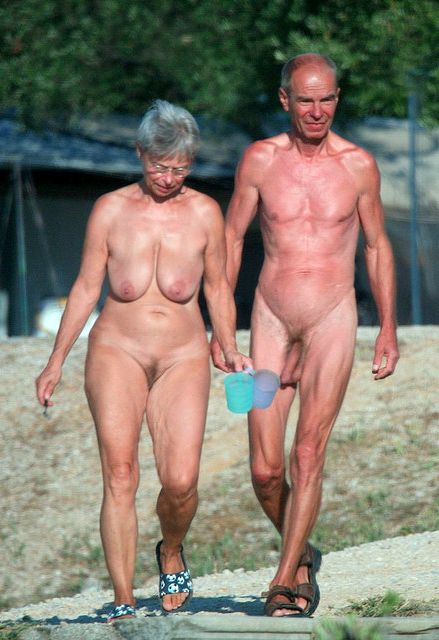 Mature couples rest on the beach fully naked