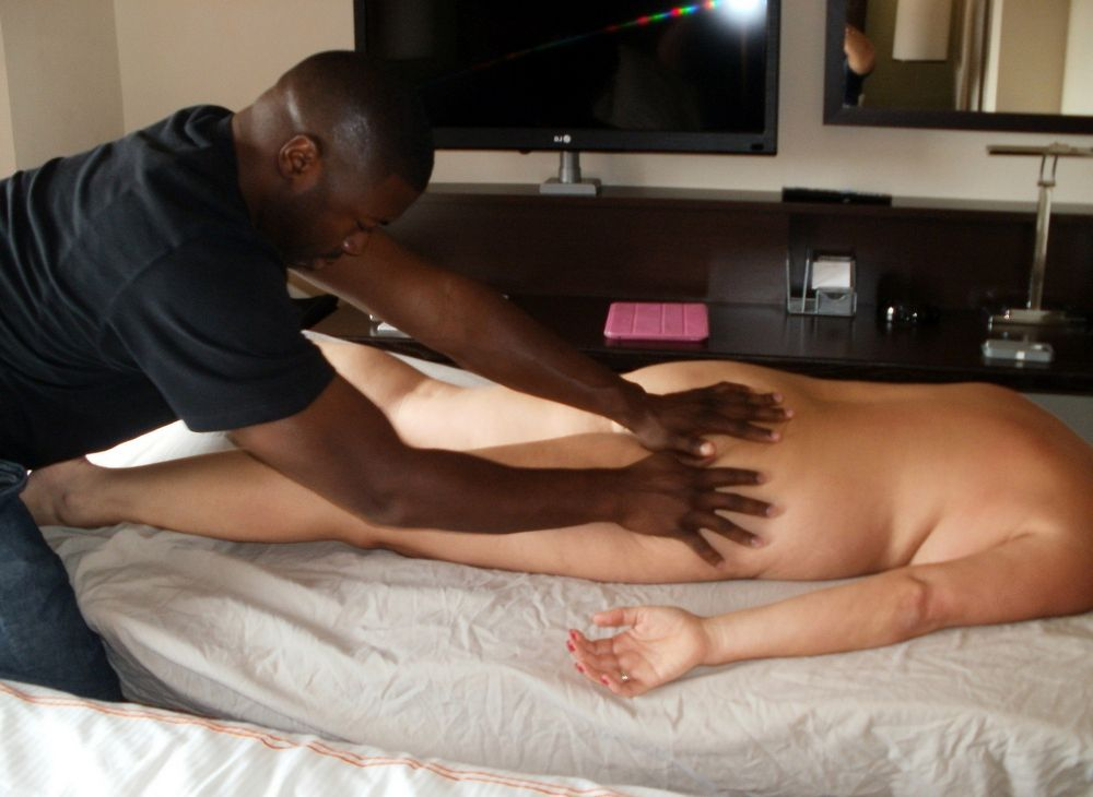 Black masseuse caresses an old whore in the salon of erotic massage for women