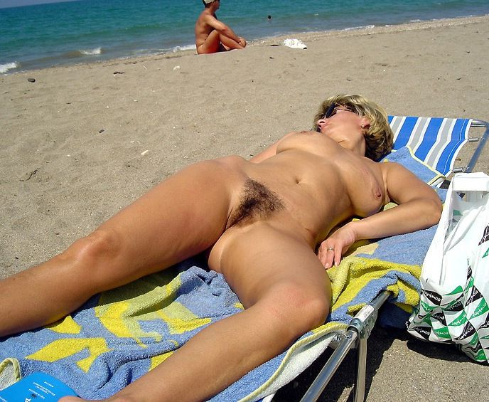 Naked old milf spreads her legs on the beach, I can see her beautiful pussy