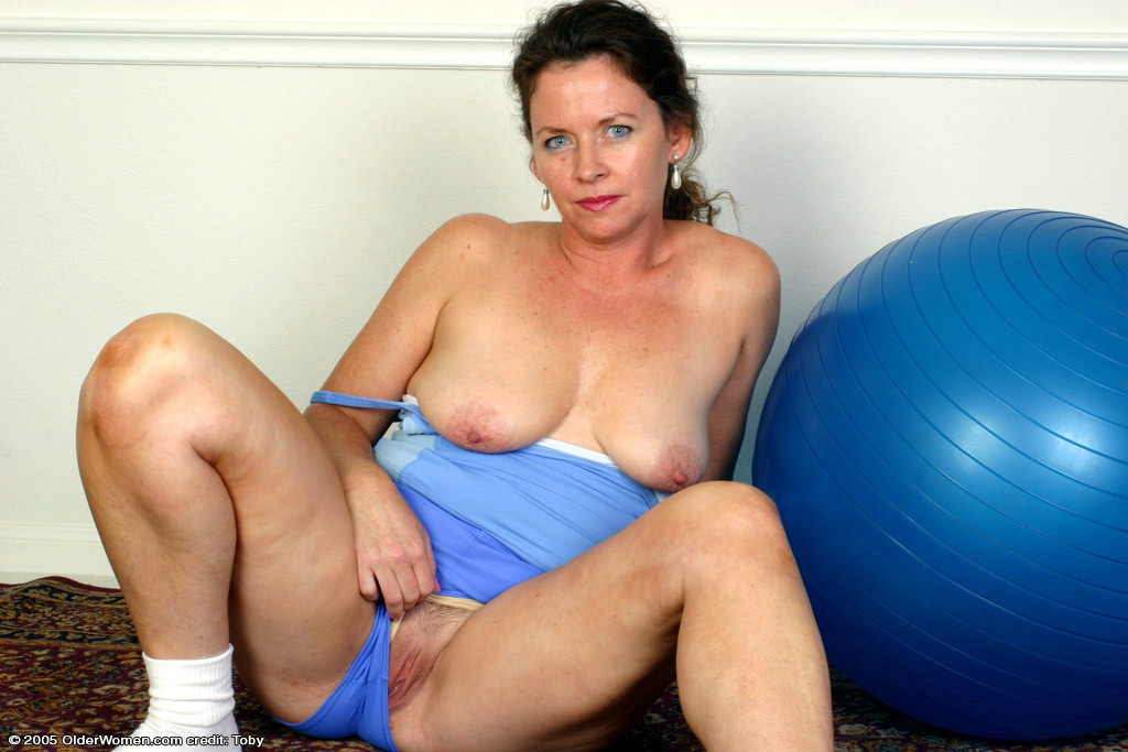 Older woman posing nude on the carpet